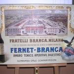 Fig. 16. «Veduta del nuovo stabilimento Branca, a Milano», 1906 circa, olio e stampa tipografica su legno (Museo storico Branca, Milano)
